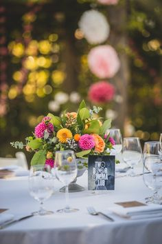 Celebrate your love of music with album themed tables instead of table numbers. Festive centerpiece includes peach and pink garden inspired arrangement with dahlias, garden roses, ranunculus, kumquats, hypericum and brunia berry and eucalyptus.