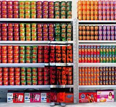 Liu Bolin poses in front of a shelf of instant noodles in a supermarket