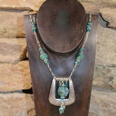 A Western inspired necklace that features an authentic fancy engraved belt buckle embellished with handmade lamp work glass beads from my studio, sterling silver findings and other metals. The necklace measures 28 inches long, the buckle is approximately 2in. X 2 in. with a SS