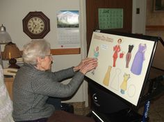 Creative Memory Boards improve Kingsway Lodge Residents' Quality of Life, Click to read the full article! Resident Kay sits in her room and dresses one of the dolls on the Dress Me Jane board