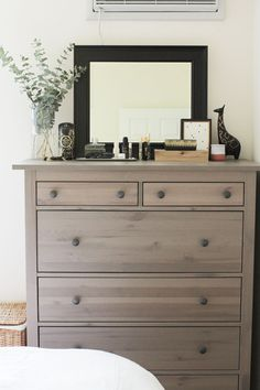 """The dresser in our bedroom always gets compliments when people come over, which makes me laugh because it's a simple piece from IKEA and is from Grant's previous apartment. It's one of a few pieces in the apartment I didn't personally choose, but I love the unique gray color of it. I am often rotating what lives on top of it, but you can always count on some form of greenery and my giraffe statue."""