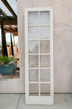 A shabby-chic window display of seating assignments | @allymagdaphoto | Brides.com