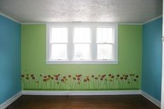 Green and turquoise painted walls with flowers along the floor board