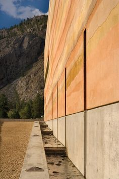 Mutli-layered rammed earth wall with sculpturally expressed weeps leading into a water feature.