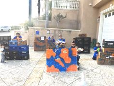 Nerf gun party. This is the other battle field . The blue team . We staked up a few cardboard boxes , spray painted them the colors of the 2 teams blue and orange . Great birthday party idea.
