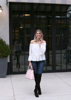 Standing in a white off the shoulder shirt with over the knee boots
