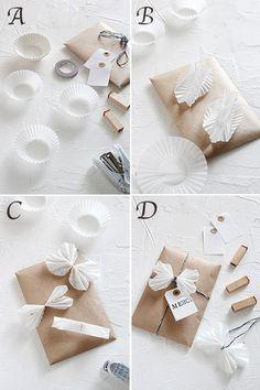 材料は多いけれど、作り方は変わらず簡単! A:ラッピングに使う材料 B:チョウチョの作り方は、おかずカップを広げてじゃばらみたいに折り畳みます。 C:二つを合わせて真ん中をホチキスで留めます。 D:畳んだところを開いてヒモやタグを使って一緒にラッピングすれば完成!