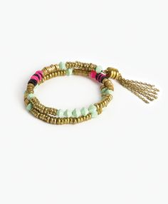 Memory wire is studded with brass discs, shell embellishments, and glass beads for an instant arm party.