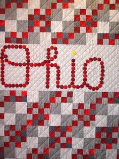 """SCRIPT OHIO""  Ohio State quilt in scarlet by Madeline Hansen.  The word ""Ohio"" is created with 102 yo-yos."