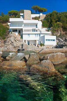 4-story white modern home built on rocky slope on the ocean.