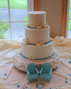 Beach wedding cake with aqua blue borders and edible chocolate seashells.  Adirondack chair toppers are a cute addition :)