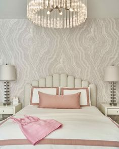 A jewelry-esque chandelier infuses glamour in this blush-toned bedroom.