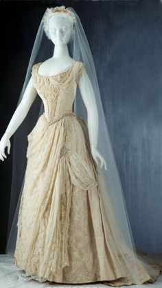 """Wedding dress & shoes, Australia, 1887. Ivory silk faille, machine Valenciennes-style lace, faux pearls and white glass beads. Fitted, boned bodice has off-shoulder neckline and very short sleeveband. Lace gathered in front to form collar. Beads applied in front to make """"stomacher."""" Pleated sash ties in front. Full, gathered skirt with bustle, overlaid with beaded lace & medallions. Pearl & bead tassle trim. Skirt lined with cream buckram. Sleeves separate from bodice. Powerhouse Museum"""