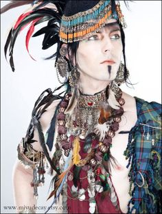 A lot going on here. Kuchi neckpiece, Scottish tartan, hipscarf as a top?, etc. Originally from Coilhouse.