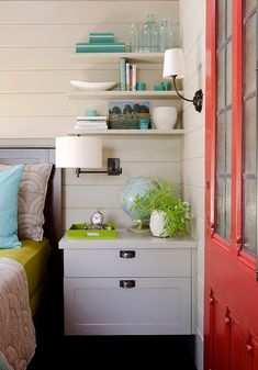 source: Kristina Crestin Design Beautiful cottage style bedroom with coral leaded glass door opening to reveal shiplap clad walls framing a wooden headboard with bed dressed with chartreuse sheets layered with white and grey duvet and shams behind an aqua blue accent pillow. The bed is flanked by a light gray floating nightstand with cup pull hardware below an oil-rubbed bronze swing arm lamp with floating shelves above topped with aqua blue accessories.