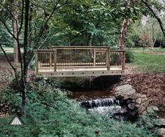 Charming Pressure Treated Wood Bridge Traverses A Small Creek Allowing Residents Easier Access To Other Areas