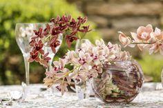 Sobre o centro da mesa, orquídeas cymbidium pendentes nos tons vinho e verde, e phalaenopsis no tom salmão, foram arranjadas por Marcinho Leme, da Milplantas, em vasos aquários transparentes de diversos tamanhos.