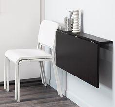Ett svart vägghängt klaffbord med två vita stolar staplade bredvid