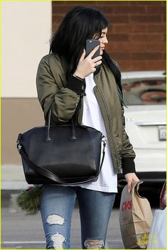 Kylie Jenner rocks long extensions, ripped jeans and a bomber jacket while out on Wednesday afternoon (October 15) in Calabasas, Calif.