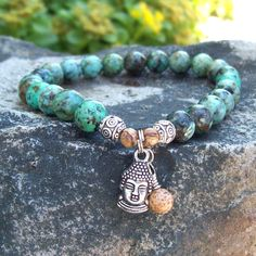 African Turquoise Buddha Charm Meditation Bracelet by Angelof2, $25.50 ~ Beaded stretch meditation bracelet in African Turquoise with accent Picture Jasper. Adorned with a Double-sided Buddha Head Charm and Picture Jasper dangle.