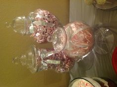 Apothecary jars filled with peppermint for a dessert table.