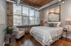 Modern industrial loft bedroom with exposed duct work [From: The Graces - ReMax Hallmark Realty]