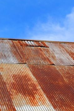 Old corrugated tinroof is rusting and patched.  Sunny blue sky and whispy clouds frame building. Stock Photo - 14865563