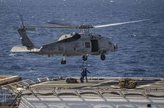 "U.S. Coast Guardsmen assigned to the Legend-class national security cutter USCGC Waesche (WMSL 751) connect a pallet to an MH-60R helicopter assigned to the ""Jaguars"" of Helicopter Maritime Strike Squadron (HSM) 60 during a vertical replenishment (VERTREP) with the Arleigh Burke-class guided-missile destroyer USS Lassen (DDG 82) in the eastern Pacific Ocean."