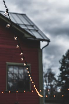 Beautiful outdoor lights outside a red house.