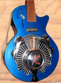 """Here's a Larry Pogreba guitar, similar to one played by Bonnie Raitt, with a carved-up hubcap from a Rambler for a resonator, """"R"""" still visible."""