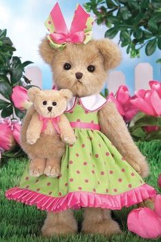 """Tulip is 14"""" in height. She is wearing a green dress with pink dots on the dress. She has a pink ribbon around the waist of the dress which is tied in a pret"""