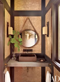 A powder room's walls are lined with cork from Innovations in Wallcoverings; the sconces are by Roman Thomas, the basin is from Vessel Sinks, and the wall-mounted sink fittings are by Rocky Mountain Hardware.