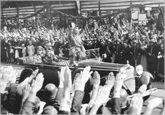 Adolf Hitler Holocaust | Standing in an open car, Adolf Hitler salutes a crowd lining the ...