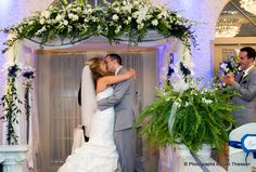Officially husband and wife, the newlyweds share a romantic kiss under their elaborate floral alter at the Versailles Ballroom, Toms River NJ. Photo courtesy of Photographs by Jan Thiessen.