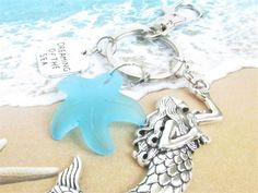 This mermaid keychain is beach inspired with its large silver tone mermaid charm, and a sea glass starfish. A sweet beach keychain which makes a perfect gift for her. Do you know a beach lover? This seaglass keychain would make an awesome gift under 20, coworker gift, or as a stocking stuffer. CARRY THE SUMMER WITH YOU ALL YEAR ROUND. There is a dreaming of the sea quote charm along with a sea glass starfish shape. MEASUREMENTS: Mermaid measures (27mm x 76mm)