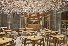 Colori e materiali a contrasto: pareti e pavimenti in calcestruzzo e arredi in legno naturale per Nozomi Sushi Bar, ristorante disegnato da Masquespacio a Valencia. Una splendida installazione a soffitto ricorda i fiori di ciliegio