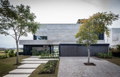 Surrounded by a lagoon and golf course, the FSY House contrasts its lush Buenos Aires landscape with a concrete facade. The exterior carries a palette of varying gray hues, relying heavily on texture from the concrete panels and lapacho wood. Concrete Facade, Concrete Houses, Exposed Concrete, Modern Shed, Modern House Design, Architecture Résidentielle, Villa, Facade House, Bungalow
