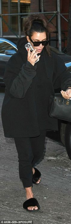 Kim added a pair of furry black slides and carried with her an older black Hermes Brikin back stuffed with her iPad. She covered her face with a large pair of sunglasses