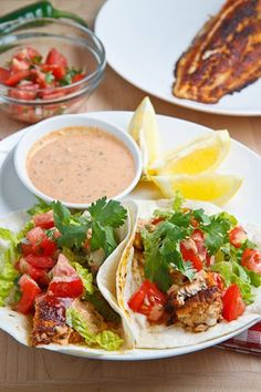 Blackened Catfish Tacos--    1 pound catfish or other white fish      1/4 cup melted butter      2 tablespoons creole seasoning      8 (6 inch) tortillas      2 cups lettuce, shredded      1 cup pico de gallo      1/4 cup remoulade sauce      hot sauce to taste