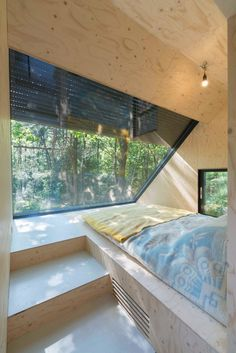 A glazed wall in this bedroom is angled to frame views of the trees overhead.