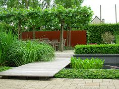 combinatie van cortenstaal, lichtkleurig tuinhout en een reliëf van verschillende soorten groen.