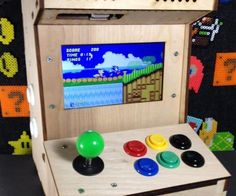 """The Porta-Pi Mini Arcade is a desktop-sized, fully functional, mini arcade cabinet measuring just under 13 x 9 x 10 inches (HxWxD). This Porta-Pi Arcade turns your Raspberry Pi in a mini arcade machine. Of course you could stuff any other retro console inside, but the RPi is so versatile, powerful and awesome that I stuck with it to build this mini arcade. The Porta-Pi Arcade Kit features: Precision Laser Cut Cabinet, made from 0.25 inch Oak Plywood . 7"""" (800x480 HDMI/VGA/Composite) LCD..."""