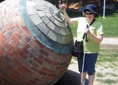 Jaimi Lard poses by a large round sculpture made of bricks and roofing tiles