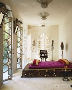 A Tuareg bed with pillows covered in silk from Uzbekistan in a guest bedroom; the chair, which was hand carved from a tree trunk, is from Ethiopia, and the cast-bronze side table is from Benin.