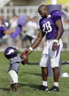 Adrian Peterson hands his son Adrian Jr. a #football during camp. #awww #sports #dad