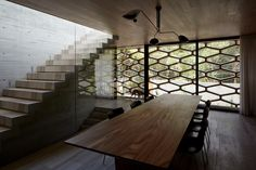 A concrete house with wood dining room table, a wall of glass, modern black light fixture, wooden block stairs and patterned hexagon screen over the facade.
