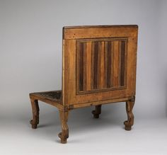 Acacia wood chair; back inlaid with strips of ebony and ivory flowers and points; seat of woven string; lion-paw feet.