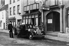Guernsey: A British policeman obligingly holds open the door of a staff car as Major-Doctor Lanz, the first German Kommandant, alights outside his Headquarters (Kommandantur) at the former Channel Islands Hotel on Glategny Esplanade, St Peter Port.