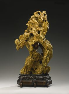 A 'YELLOW WAX' SCHOLARS ROCK  Estimation: 10,000 - 12,000 USD   the weathered surface enlivened with rhythmically spaced hollows imparting a feeling of lightness, the profile resembling a swooping eagle, the mustard-yellow rock with some orange inclusions and waxy appearance, Jiangnan-style wood stand (2)  Height 24 3/4  in., 62.8 cm