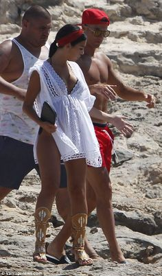 Happy together: Cristiano Ronaldo's 'pregnant' girlfriend Georgina Rodriguez covered her 'bump' in a loose-fitting mini dress as she held hands with the shirtless sportsman on a family beach holiday in Formentera on Tuesday